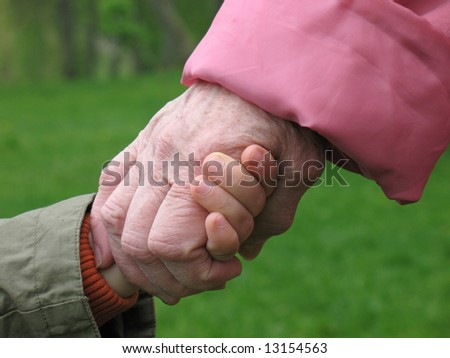 grandson and grandmother holding hands - stock photo
