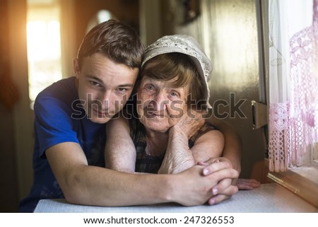 Grandson hugging her grandmother posing for a portrait. - stock photo
