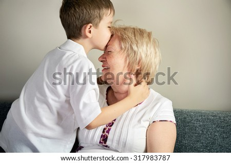 grandson kissing his grandmother horizontal - stock photo