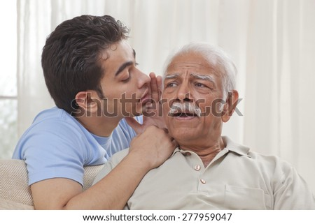 Grandson whispering into grandfather's ear - stock photo