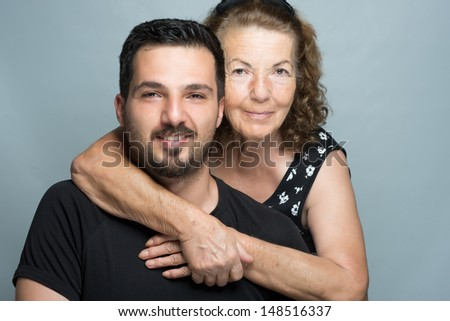 Grandson with his grandmother hugging each other - stock photo