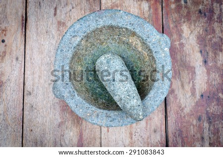 Granite Mortar and Pestle on wood table - stock photo