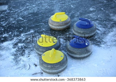granite stones for curling on ice of frozen lake - stock photo