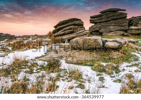 Granite tor on frosty morning    at sunrise in Dartmoor, England. - stock photo