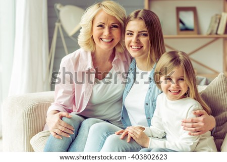 Granny, her daughter and granddaughter are looking at camera and smiling while sitting on sofa at home - stock photo
