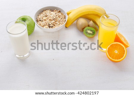 Granola, bananas, glass of orange juice, kiwi, and a glass of milk on a light wooden surface with free space for your text. Food for a healthy and tasty food - stock photo