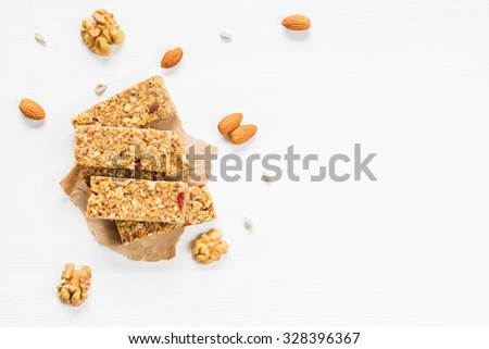 Granola bar or energy bar with oats, dates and nuts on white wooden background, top view - stock photo