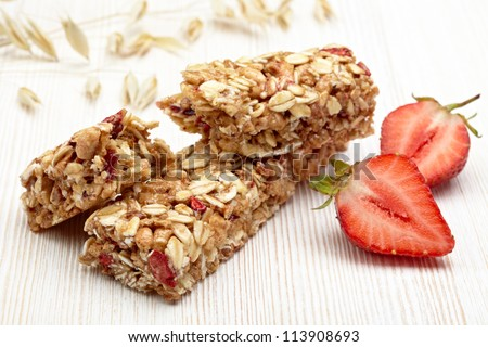 Granola bar with strawberries on white wooden background - stock photo