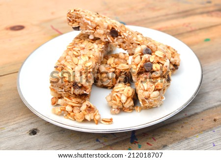 Granola bars with chocolate in white plate on wooden board  - stock photo