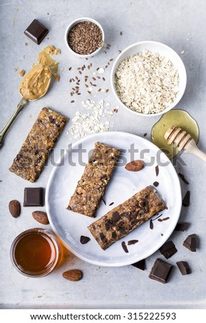 Granola bars with several ingredients near them shot from above - stock photo