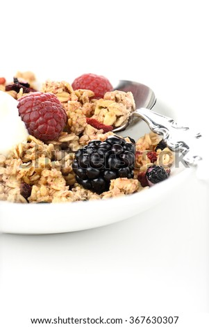 Granola breakfast muesli on a spoon with currants and fresh fruit against a white background. Concept image for healthy eating. Copy space. - stock photo
