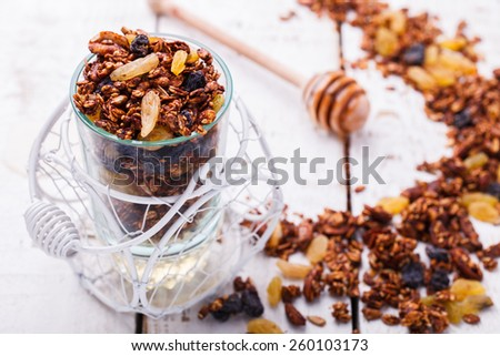 Granola, honey, raisins, peanuts and sunflower seeds. - stock photo