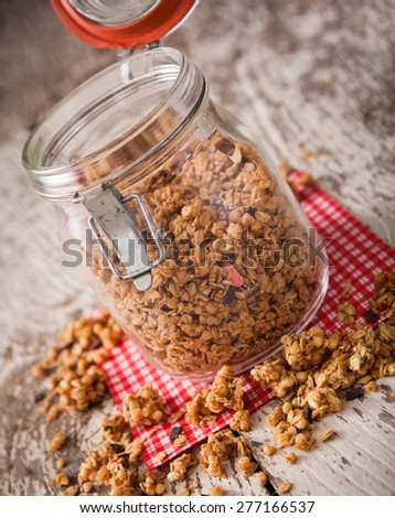 Granola in open glass jar on rustic wooden background - stock photo