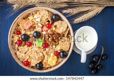 Granola ( muesli ) with red and black currants and milk in a jug - stock photo
