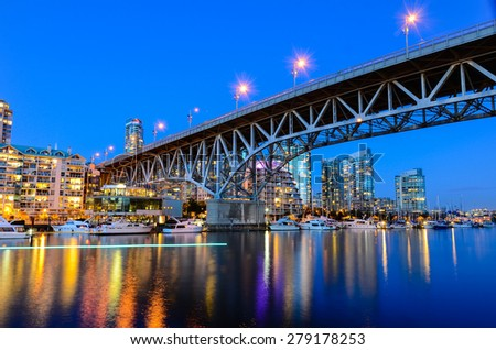 Granville Bridge along False Creek at Night in Vancouver BC. The light on creek's surface is made by slow speed water taxi. - stock photo