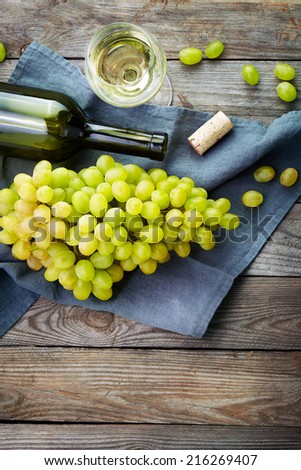 Grape, a bottles and glass of  white wine with grape on wooden table - stock photo