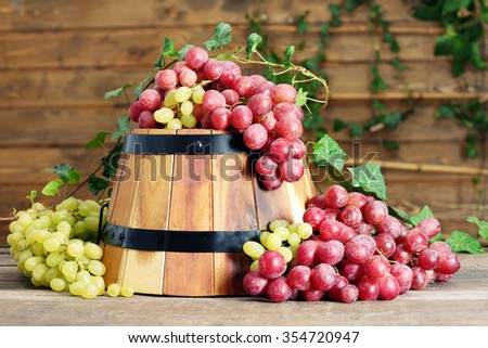 Grape and barrel on wooden table - stock photo
