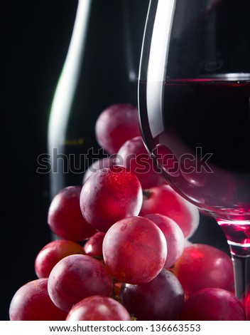 grape and glass with red wine on a black background - stock photo
