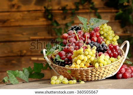 Grape in basket on wooden table - stock photo