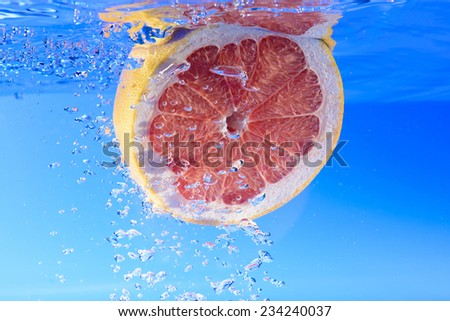 Grapefruit in water with bubbles - stock photo
