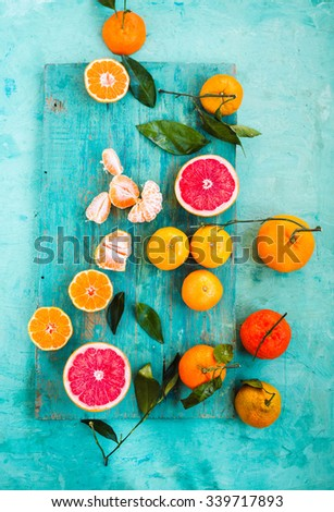 Grapefruit, mandarin, clementine sliced with leaves over on a light blue table. Colorful festive still life. - stock photo