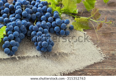 Grapes blue on a old wooden table. - stock photo