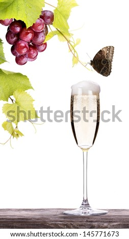 grapes, butterfly with glass of champagne on a wooden vintage table isolated on a white baclground - stock photo