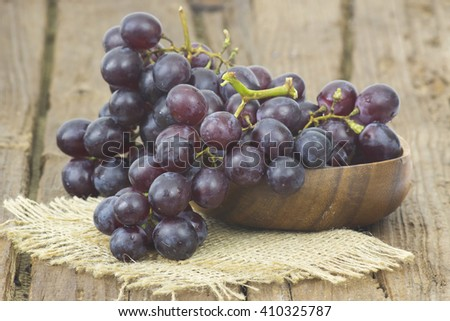 grapes in a bowl on wooden background - stock photo