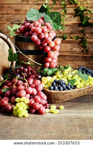 Grapes in bowl and barrel on wooden table - stock photo
