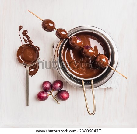 Grapes in chocolate making on white wooden background, top view - stock photo