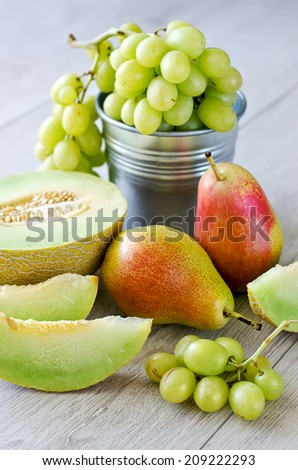 Grapes, melon and pears, wooden background - stock photo