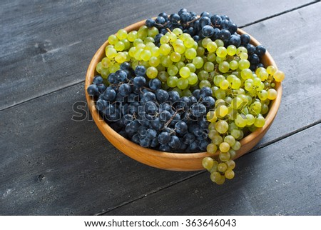 grapes on wooden bowl, black wood table background - stock photo
