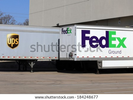 GRAPEVINE, TX - MARCH 14: UPS and Fedex trailers parked next to each other at a loading dock on March 14, 2014. The shipment and logistics companies are perennial competitors. - stock photo