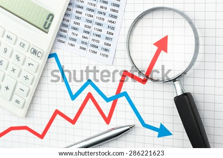 Graph, chart, magnifying glass, calculator and pen. Looking growth field of line graph with magnifying glass. Line graph and magnifying glass. Analyzing data.  - stock photo