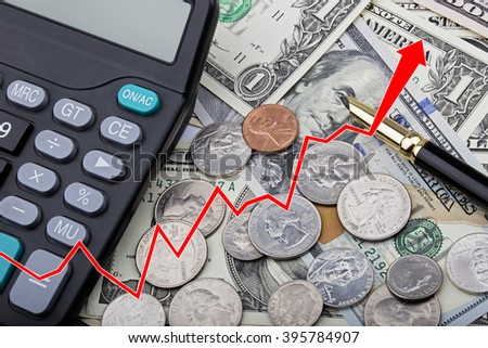 Graph showing United States bank notes and coins with a calculator and pen - stock photo