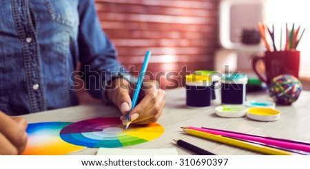 Graphic designer drawing on colour chart at workplace - stock photo