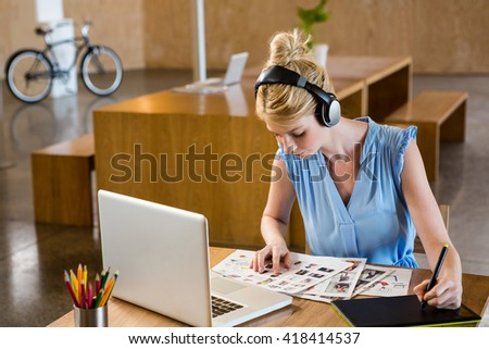 Graphic designer looking at chart while using graphic tablet in office - stock photo