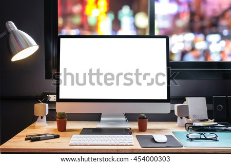 Graphic designer's workspace with city night view with a pen tablet, a computer and white background for text - stock photo
