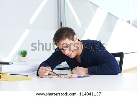 Graphic designer sitting with color fans and pencil in his office - stock photo