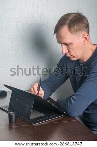 Graphic designer using digital tablet and computer at home - stock photo