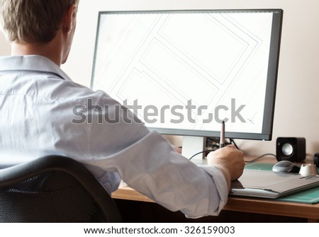 Graphic designer using digital tablet and computer in office or home - stock photo