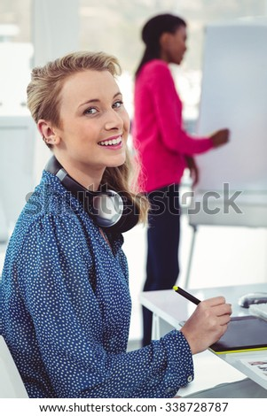 Graphic designer wearing headphones at desk in casual office - stock photo