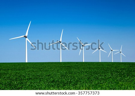 Graphic modern landscape of wind turbines aligned in a green and yellow field - stock photo