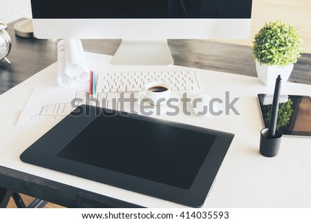 Graphic tablet on designer desktop with computer monitor and keyboard, construction sketch, coffee cup and other items - stock photo