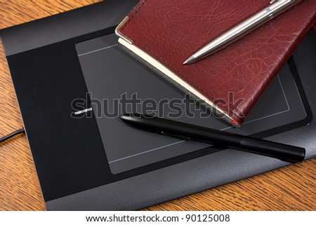 Graphic tablet on wooden table with digital pen, notebook and pencil - stock photo