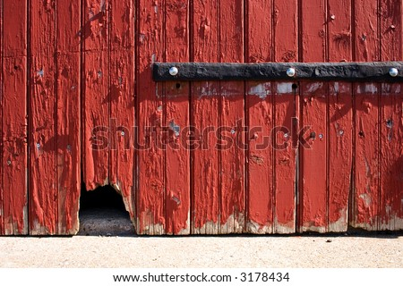 graphical photograph of a barn door with a mouse hole - stock photo