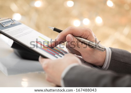graphs and charts analyzed by businessman with coffee - stock photo