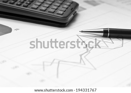 Graphs, calculator and paper statements for finance concept - stock photo