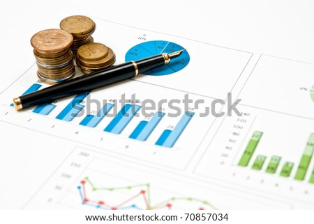 Graphs, charts and pen with stacks of coins - stock photo