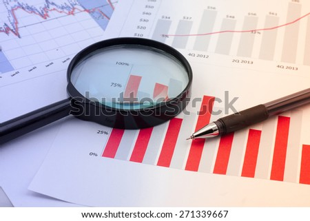 Graphs, magnifier and pen. Analysis charts and graphs of sales. - stock photo